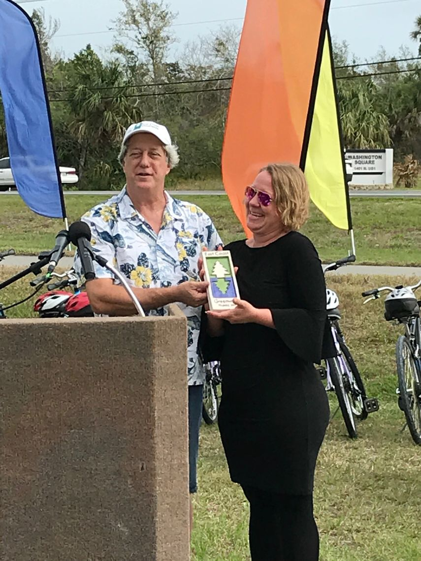 Paul Haydt, Florida coordinator for the East Coast Greenway Alliance, presents a commemorative Greenway tile to Robin Birdsong, director of Florida's SUN Trail program during the Titusville ribbon-cutting ceremonies.
