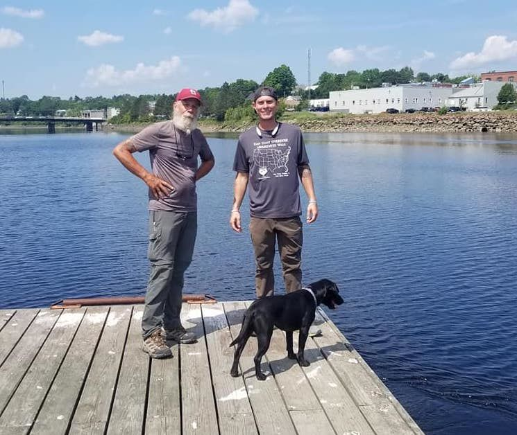John Azerolo, left, and Brett Bramble (and Brett's dog, Domino) on the St. Croix River in Calais, ME, on July 31, 2018, six months since leaving Key West to walk the East Coast Greenway to raise awareness of drug overdoses.