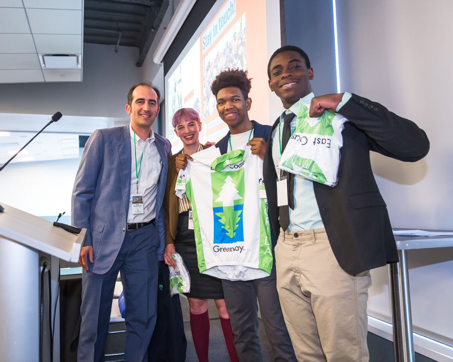 Executive Director Dennis Markatos-Soriano presents Greenway bike jerseys to Taylor Kuyk-White, youth cycling manager for Bicycle Coalition of Greater Philadelphia, and Emir Johnson and Jahmiel Jackson, members of the Youth Advisory Committee who welcomed Summit attendees and shared their stories of what cycling means to them.