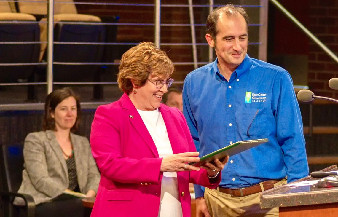 2019: Cary, North Carolina, Mayor Pro Tem Lori Bush reads a proclamation honoring National Bike Month and the East Coast Greenway before presenting it to Executive Director Dennis Markatos-Soriano.